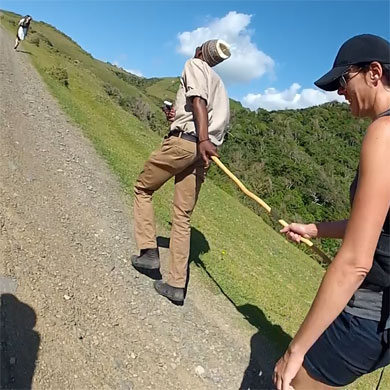 A guide helps a hiker up a hill